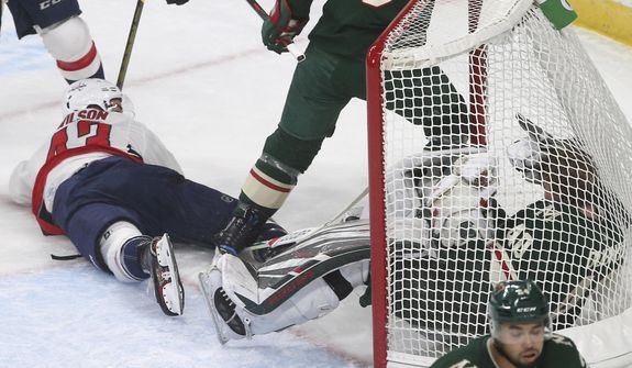 Washington Capitals' Tom Wilson, top left, looks back on his goal against Minnesota Wild goalie Devan Dubnyk, right, crashing into him in the first period of an NHL hockey game Tuesday, Nov. 13, 2018, in St. Paul, Minn. Wilson returned to the lineup after his 20-game suspension was reduced to 14 by a neutral arbitrator. After the goal Wilson received a two-minute penalty for goaltender interference. (AP Photo/Jim Mone)
