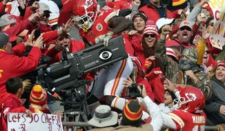 Kansas City Chiefs quarterback Patrick Mahomes (15) watches as wide receiver Tyreek Hill (10) climbs behind a television camera following his touchdown, during the first half of an NFL football game against the Arizona Cardinals in Kansas City, Mo., Sunday, Nov. 11, 2018. Hill drew a penalty on his celebration. (AP Photo/Ed Zurga)