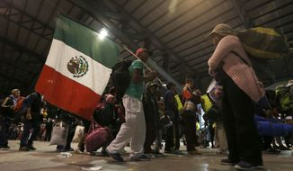 Central American migrants moving as a caravan toward the U.S. border, one carrying a Mexican flag, get ready to leave Benito Juarez Auditorium that sheltered them overnight in Guadalajara, Mexico, Tuesday, Nov. 13, 2018. Many say they are fleeing rampant poverty, gang violence and political instability primarily in the Central American countries of Honduras, Guatemala, El Salvador and Nicaragua. (AP Photo/Marco Ugarte)