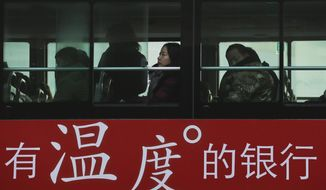 "Commuters look out of a window of a bus with a bank advertise during the morning rush hour in Beijing, Tuesday, Nov. 13, 2018. The potential damage to global trade brought on by President Donald Trump's tariffs battle with Beijing is looming as leaders of Southeast Asian nations, China, the U.S. and other regional economies meet in Singapore this week. The advertisement reads ""A warm-hearted bank.""  (AP Photo/Andy Wong)"