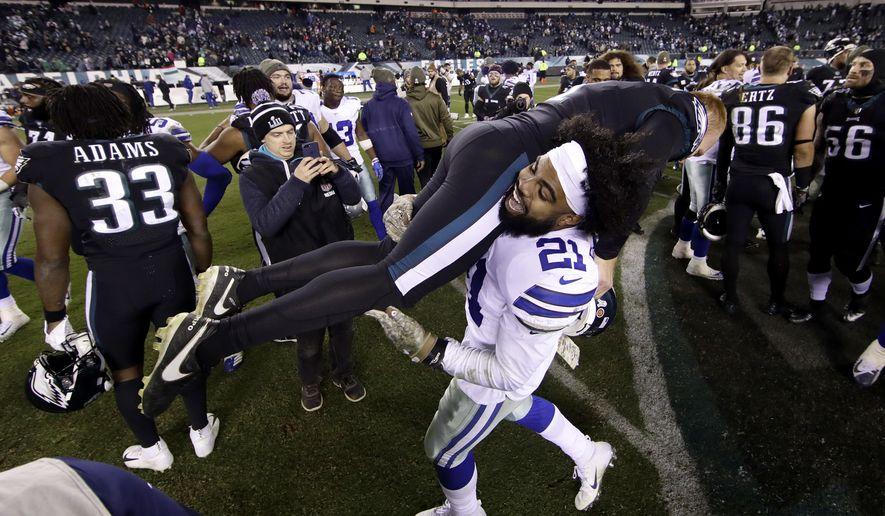 Dallas Cowboys running back Ezekiel Elliott (21) carries Philadelphia Eagles punter Cameron Johnston (1) after an NFL football game, Sunday, Nov. 11, 2018, in Philadelphia. The Cowboys won 27-20. (AP Photo/Matt Rourke)