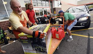 FILE - In this Sept. 10, 2018 file photo, Jim Craig, David Burke and Chris Rayner load generators as people buy supplies at The Home Depot in Wilmington, N.C. Home Depot Inc. reports earnings Tuesday, Nov. 13. (Ken Blevins/The Star-News via AP, File)