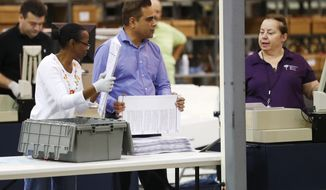 Employees at the Palm Beach County Supervisor of Elections office feed ballots through a machine as they count votes during a recount, Tuesday, Nov. 13, 2018, in West Palm Beach, Fla. (AP Photo/Wilfredo Lee)