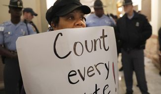 A woman holds a sign as state troopers look on during a protest in the rotunda of the state capitol building Tuesday, Nov. 13, 2018, in Atlanta.  Several protesters, including a state senator, have been arrested during a demonstration at the Georgia state Capitol calling for tallying of uncounted ballots from last week's election. (AP Photo/John Amis)