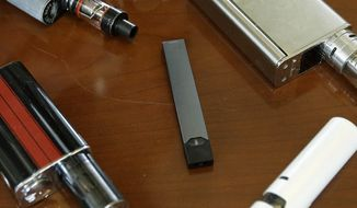 This Tuesday, April 10, 2018, file photo shows vaping devices, including a Juul, center, that were confiscated from students at a high school in Marshfield, Mass. On Tuesday, Nov. 13, 2018, San Francisco-based Juul Labs Inc. announced it had stopped filling orders for its mango, fruit, creme and cucumber pods but not menthol and mint. It will sell all flavors through its website and limit sales to those 21 and older. (AP Photo/Steven Senne)