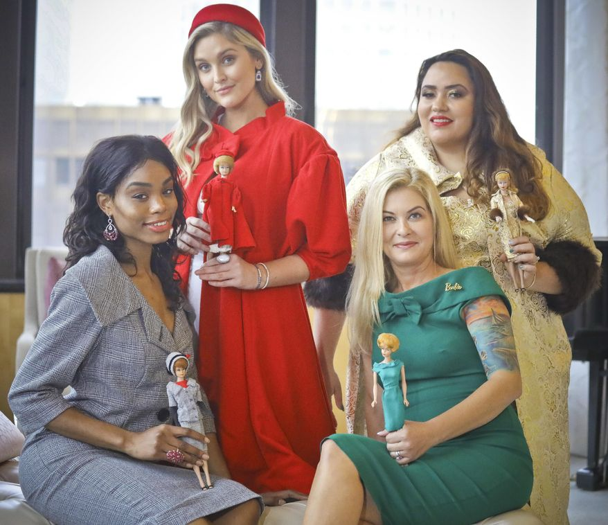 In this Nov. 5, 2018 photo, designer Katie Echeverry, seated right, join models Tiffany Hendrix, seated left, Kelsey Elliott, standing left, and Lori Moran, wearing outfits from a Barbie inspired fashion line she created in collaboration with toy company Mattel in New York. The collaboration, Barbie x Unique Vintage, is sold online at uniquevintage.com and in about 500 boutiques around the world.  (AP Photo/Bebeto Matthews)