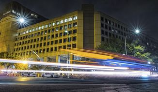 In this Nov. 1, 2017, file photo, traffic along Pennsylvania Avenue in Washington streaks past the Federal Bureau of Investigation headquarters building. (AP Photo/J. David Ake)