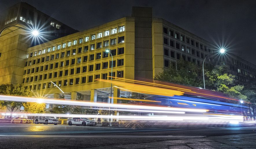 In this Nov. 1, 2017, file photo, traffic along Pennsylvania Avenue in Washington streaks past the Federal Bureau of Investigation headquarters building. (AP Photo/J. David Ake)