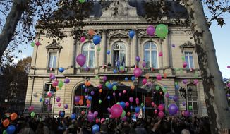 Balloons are released in front of the Paris 11th district town hall during a ceremony marking the third anniversary of the Paris attacks of November 2015 in which 130 people were killed, in Paris, Tuesday, Nov. 13, 2018. France's interior minister says French security services have foiled six terror attacks this year, as the country marks three years since gun and bomb attacks in Paris killed 130 people. (AP Photo/Christophe Ena)