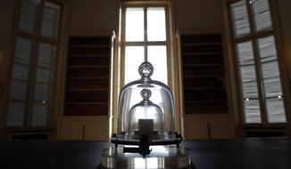 In this photo taken Wednesday, Oct. 17, 2018., a replica of the International Prototype Kilogram is pictured at the International Bureau of Weights and Measures, in Sevres, near Paris. The golf ball-sized metal cylinder at the heart of the world's system for measuring mass is heading into retirement. Gathering this week in Versailles, west of Paris, governments on Friday Nov. 16, 2018, are expected to approve a plan to instead use a scientific formula to define the exact weight of a kilo. (AP Photo/Christophe Ena)