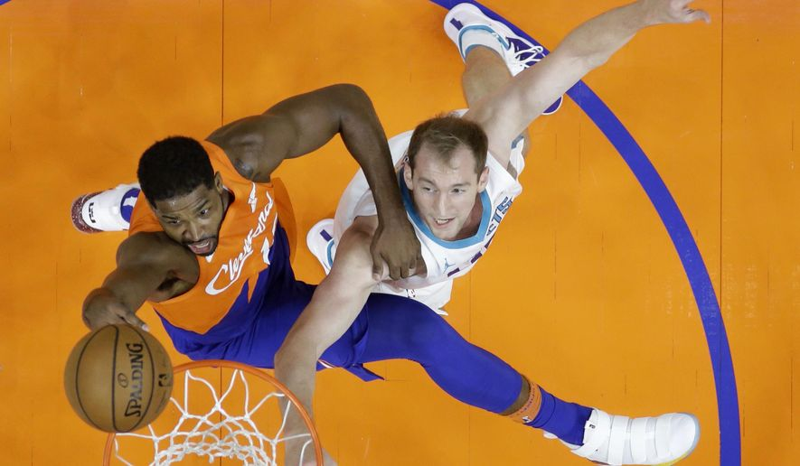 Cleveland Cavaliers' Tristan Thompson, left, drives to the basket against Charlotte Hornets' Cody Zeller in the first half of an NBA basketball game, Tuesday, Nov. 13, 2018, in Cleveland. (AP Photo/Tony Dejak)