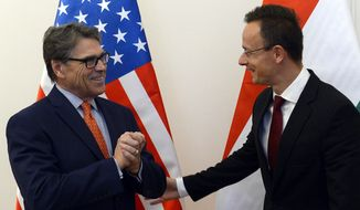 Hungarian Minister of Foreign Affairs and Trade Peter Szijjarto, right, welcomes US Secretary of Energy Rick Perry at the Ministry of Foreign Affairs and Trade in Budapest, Hungary, Tuesday, Nov. 13, 2018. (Lajos Soos/MTI via AP)
