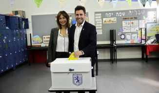 Mayoral candidate Ofer Berkovitch, right, and his wife Dina pose for the media as they cast their votes at a polling station in Jerusalem, Tuesday, Nov. 13, 2018. Israelis were choosing their next mayors in dozens of locations across the country Tuesday, with the main focus on the largest city of Jerusalem. (AP Photo/Mahmoud Illean)