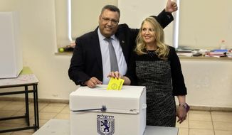 Mayoral candidate Moshe Lion, left, and his wife pose for the media as they cast their votes at a polling station in Jerusalem, Tuesday, Nov. 13, 2018. Israelis were choosing their next mayors in dozens of locations across the country Tuesday, with the main focus on the largest city of Jerusalem. (AP Photo/Mahmoud Illean)