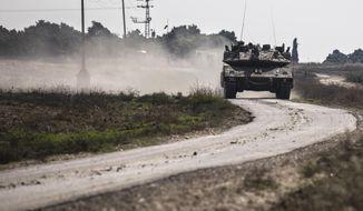 An Israeli tank drives near the Israel Gaza border, Tuesday, Nov. 13, 2018. (AP Photo/Tsafrir Abayov)