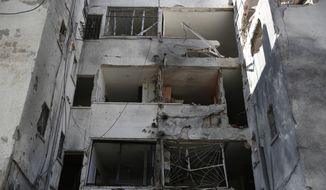 The facade of an apartment building shows damage after it was hit by a rocket fired by Palestinian militants from Gaza , in the southern Israeli city of Ashkelon, Israel, Tuesday, Nov. 13, 2018. (AP Photo/Ariel Schalit)