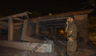 An Israeli soldier walks by a house damaged by a missile fired from the Gaza Strip in the southern Israeli city of Ashkelon, Monday, Nov. 12, 2018. Palestinian militants bombarded Israel with dozens of rockets and mortar shells Monday, while Israeli warplanes struck targets throughout the Gaza Strip in what appeared to be the most intense exchange of fire since a 2014 war. (AP Photo/Tsafrir Abayov)