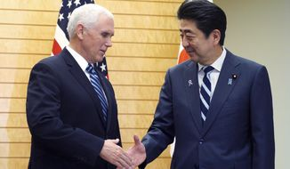 U.S. Vice President Mike Pence, left, and Japanese Prime Minister Shinzo Abe shake hands at Abe's official residence in Tokyo Tuesday, Nov. 13, 2018. (AP Photo/Eugene Hoshiko)