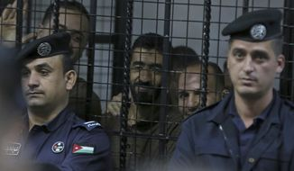 Guards surround the defendants' cage in state security court as judges sentenced 10 defendants to prison, with terms ranging from three years to life, for their role in an Islamic State attack on the Karak castle, a popular tourist site, Tuesday, Nov. 13, 2018, in Amman Jordan. The December 2016 attack killed 14 people, including a Canadian tourist and marked the first time IS extremists claimed responsibility for a large-scale attack on a civilian site in Jordan. (AP Photo/Raad Adayleh)