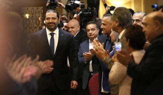 Journalists and supporters of Lebanese Prime Minister--designate Saad Hariri, left, clap as he arrives for a press conference, in Beirut, Lebanon, Tuesday, Nov. 13, 2018. Hariri accused Hezbollah of hindering the formation of a new government six months after parliamentary elections. He said the Shiite militant group bears full responsibility for the consequences, including Lebanon's flagging economy. (AP Photo/Hussein Malla)