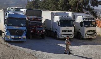 In this Oct. 31, 2018 photo, a Lebanese customs officer walks past trucks waiting to cross into Syria from the Lebanese border crossing point of al-Masnaa, in Bekaa Valley, Lebanon. The long-awaited reopening of a vital border crossing between Syria and Jordan earlier this month was supposed to bring relief to Lebanese farmers and traders looking to resume exports to Gulf countries. But the commerce has so far been complicated by politics, high transit fees and fighting over which trucks pass through which country. (AP Photo/Hussein Malla)