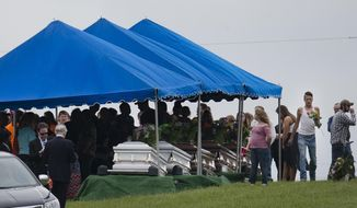 In this May 3, 2016, file photo, mourners gather around caskets for six of the eight members of the Rhoden family found shot April 22, 2016, at four properties near Piketon, Ohio, during funeral services at Scioto Burial Park in McDermott, Ohio. Authorities say Tuesday, Nov. 13, 2018, that a family of four has been arrested in in the slayings of eight members of one family in rural Ohio two years ago. (AP Photo/John Minchillo, File)