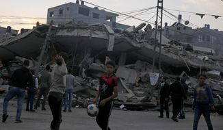 Palestinians gather in front of a destroyed building that was hit by Israeli airstrikes, in Gaza City, Tuesday, Nov. 13, 2018. (AP Photo/Hatem Moussa)