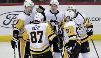 Pittsburgh Penguins players celebrate a goal by left wing Jake Guentzel, back right, during the third period of an NHL hockey game against the New Jersey Devils, Tuesday, Nov. 13, 2018, in Newark, N.J. The Devils won 4-2. (AP Photo/Julio Cortez)