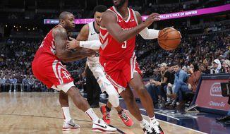 Houston Rockets guard Chris Paul, front, drives to the basket as forward PJ Tucker, back left, blocks Denver Nuggets guard Jamal Murray in the first half of an NBA basketball game, Tuesday, Nov. 13, 2018, in Denver. (AP Photo/David Zalubowski)