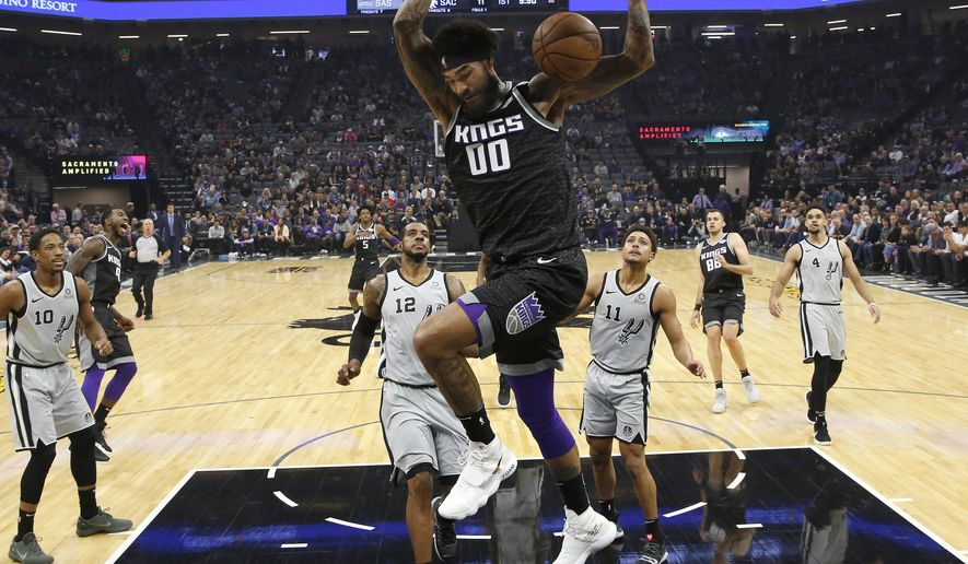 Sacramento Kings center Willie Cauley-Stein, center, stuffs as San Antonio Spurs' LaMarcus Aldridge (12) ands Bryn Forbes, (11) look on during the first quarter of an NBA basketball game Monday, Nov. 12, 2018, in Sacramento, Calif. (AP Photo/Rich Pedroncelli)