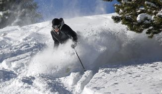A skier makes a turn in fresh snow on Breckenridge Ski Resort's opening day Wednesday, Nov. 7, 2018, in Breckenridge, Colo. The resort opened early after receiving more than 5 feet of snow already this season. (Hugh Carey/Summit Daily News via AP)