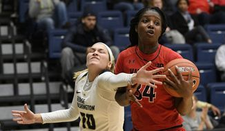 George Washington forward Sarah Overcash, left, fights for the ball against Maryland forward Brianna Fraser (34) during the first half of an NCAA college basketball game, Wednesday, Nov. 14, 2018, in Washington. (AP Photo/Nick Wass)