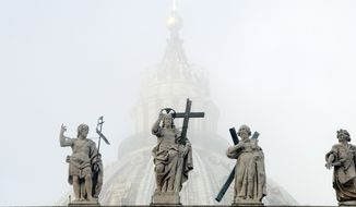 The dome of St. Peter's Basilica is partially engulfed in the fog behind statues of saints adorning the colonnade designed by 16th century Italian sculptor and architect Gian Lorenzo Bernini, in St. Peter's Square, at the Vatican, Wednesday, Nov. 14, 2018. (AP Photo/Andrew Medichini)