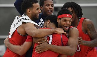 Teammates mob Robert Morris guard Josh Williams, back to camera, after he tied the NCAA record with 15 3-point baskets, against Mount Aloysius in a college basketball game Wednesday, Nov. 14, 2018, in Moon Township near Pittsburgh. (Peter Diana/Pittsburgh Post-Gazette via AP)