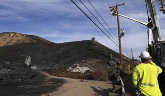 Southern California Edison crews work to replace burned power poles and lines destroyed by the Woolsey Fire over a burned-over hillside along Pacific Coast Highway in Malibu, southern California, Tuesday, Nov. 13, 2018. (AP Photo/Reed Saxon)