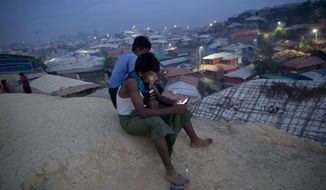 Rohingya Muslims use their cellphones as they sit on a hillock overlooking Balukhali refugee camp, in Bangladesh, Wednesday, Nov. 14, 2018. Bangladesh authorities said they are ready to begin repatriating some of the more than 700,000 Rohingya Muslims who have fled from army-led violence in Myanmar since last year, but refugees scheduled to leave said they would refuse to go because of fears for their safety. (AP Photo/Dar Yasin)