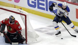 St. Louis Blues right wing Vladimir Tarasenko, right, looks to pass the puck as Chicago Blackhawks goalie Corey Crawford watches during the third period of an NHL hockey game Wednesday, Nov. 14, 2018, in Chicago. The Blackhawks won 1-0. (AP Photo/Nam Y. Huh)