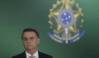 Brazil's President-elect Jair Bolsonaro attends a joint statement with Brazil's president, after a meeting at the Presidential Palace, in Brasilia, Brazil, Wednesday, Nov. 7, 2018. (AP Photo/Eraldo Peres)