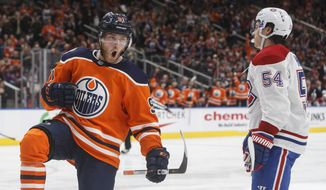 Montreal Canadiens' Charles Hudon (54) skates past as Edmonton Oilers' Drake Caggiula (91) celebrates a goal during the second period of an NHL hockey game, Tuesday, Nov. 13, 2018 in Edmonton, Alberta. (Jason Franson/The Canadian Press via AP)