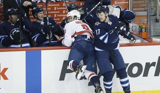 Winnipeg Jets' Adam Lowry (17) checks Washington Capitals' Alex Ovechkin (8) during first period NHL hockey action in Winnipeg, Manitoba on Wednesday, Nov. 14, 2018. (John Woods/The Canadian Press via AP)