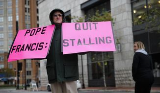 Robert Hoatson, of West Orange, N.J., holds protest signs outside of a hotel hosting the United States Conference of Catholic Bishops' annual fall meeting, Tuesday, Nov. 13, 2018, in Baltimore. (AP Photo/Patrick Semansky)