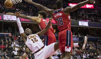 Cleveland Cavaliers guard David Nwaba (12) tries to shoot past Washington Wizards forward Kelly Oubre Jr. (12) and center Ian Mahinmi (28), from France, during the first half of an NBA basketball game Wednesday, Nov. 14, 2018, in Washington. (AP Photo/Alex Brandon)