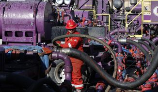 FILE - In this March 25, 2014 file photo, a worker adjusts hoses during a hydraulic fracturing operation at a gas well, near Mead, Colorado. The U.S. Environmental Protection Agency is holding its only public hearing on the Trump administration's plans to roll back Obama-era rules for methane pollution from the oil and gas industry. Nearly 125 people have asked to speak at the daylong session in Denver on Wednesday, Nov. 14, 2018. (AP Photo/Brennan Linsley, File)