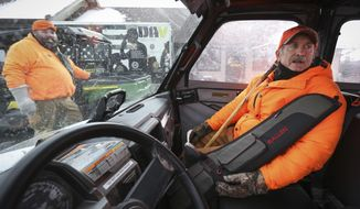 ADVANCE FOR USE MONDAY, NOV. 19 - In this Friday, Nov. 9, 2018 photo, veteran Tom McLaughlin, right, readies himself for a ride to a deer blind in Chester Woods Park in Olmsted County, Minn., with help from Nate Pike, left, of Olmsted County Veterans Services. Olmsted County has closed the park for about two weeks to allow hunts to manage the deer herd in the park. Disabled veterans get an opportunity to hunt for four of those days. (Ken Klotzbach/The Rochester Post-Bulletin via AP)