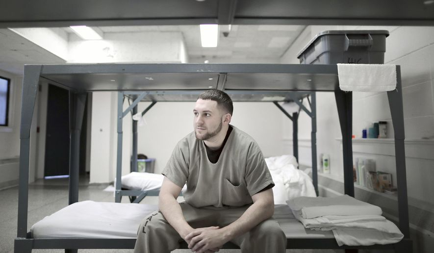 Rock County Jail inmate Austin Temple sits on the edge of his bed inside the dormitory for those enrolled in the Rock County Education and Criminal Addiction Program on Monday, November 5, 2018, in Janesville, Wis.  (Anthony Wahl/The Janesville Gazette via AP)