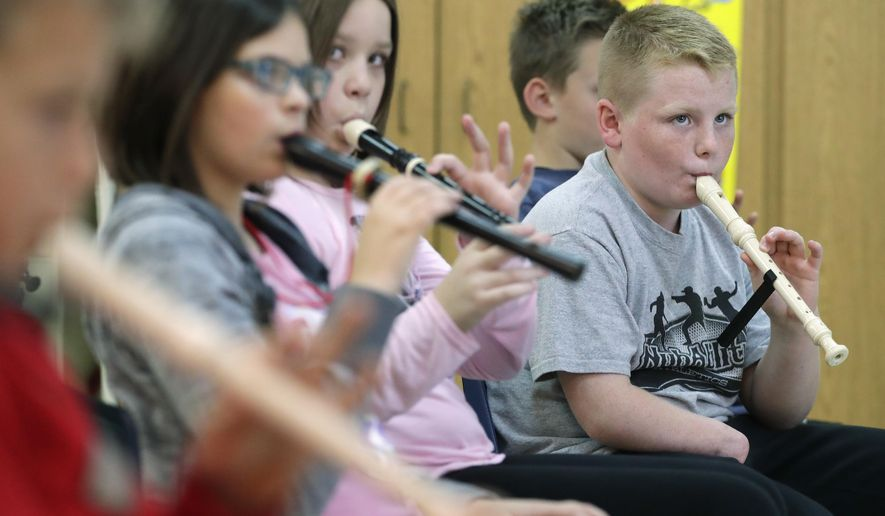 Fourth-grader Isaiah Lanphear learns to play the recorder with his classmates on Nov. 7, 2018 at Wrighstown Elementary School. Lanphear, who lost his hand in a lawn mowing accident, uses a device made by a 3D printer to help him hold the musical instrument. (Sarah Kloepping /The Post-Crescent via AP)