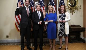 House Speaker Paul Ryan of Wis., left, ceremonially swears-in Rep.-elect Mary Gay Scanlon, D-Pa., second from right, as her husband Mark Stewart holds the Bible, Tuesday Nov. 13, 2018, in the speaker's ceremonial office on Capitol Hill in Washington. Scallion will fill a vacancy for the remainder of the 115th Congress. At right is their daughter, Casey Stewart. (AP Photo/Jacquelyn Martin)
