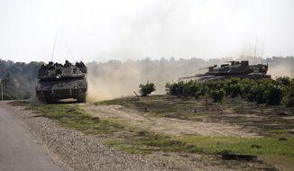 Israeli tanks move near the Israel Gaza border, Tuesday, Nov. 13, 2018. (AP Photo/Tsafrir Abayov)
