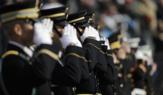 Military personnel salute during pregame ceremonies before an NFL football game between the Chicago Bears and Detroit Lions Sunday, Nov. 11, 2018, in Chicago. (AP Photo/Nam Y. Huh)