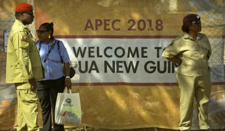 Security officials stand outside a perimeter fence for a secured area ahead of the APEC Economic Leaders' Week Summit in Port Moresby, Papua New Guinea, Wednesday, Nov. 14, 2018. After three decades of promoting free trade as a panacea to poverty, the APEC grouping of nations that includes the U.S. and China is holding its lavish annual leaders meeting in the country that can least afford it. (AP Photo/Mark Schiefelbein)
